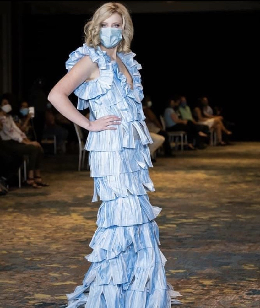 Paris Taylor posing on the runway in the designer dress and a mask on her face