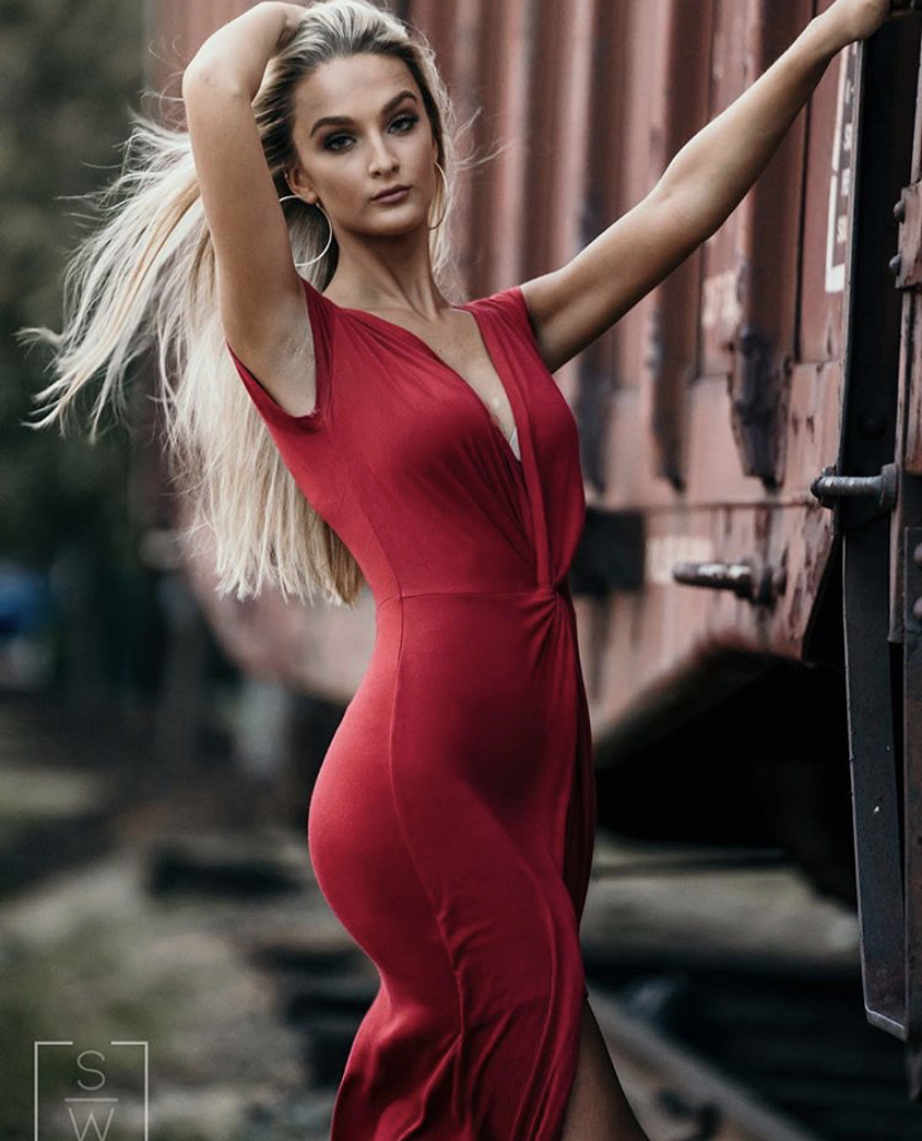 Body shot of Madison in a red dress reclining next to a railroad car